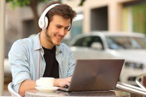 man smiling at his laptop