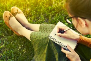 woman sat on grass drawing on a notebook