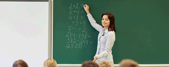 teacher writing in chalk on board
