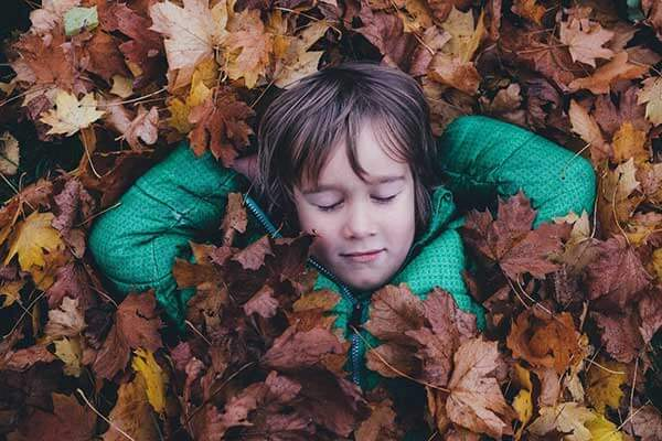 Child lying in leaves